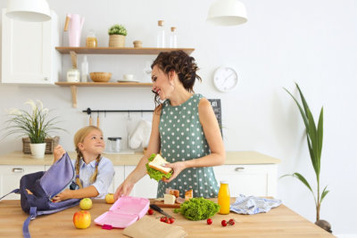 adult woman and young child packing healthy food