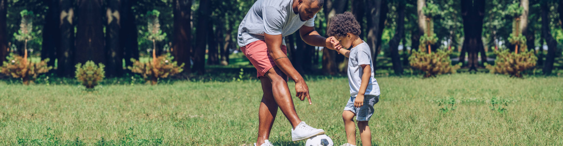 young man teaching adorable son playing football in park
